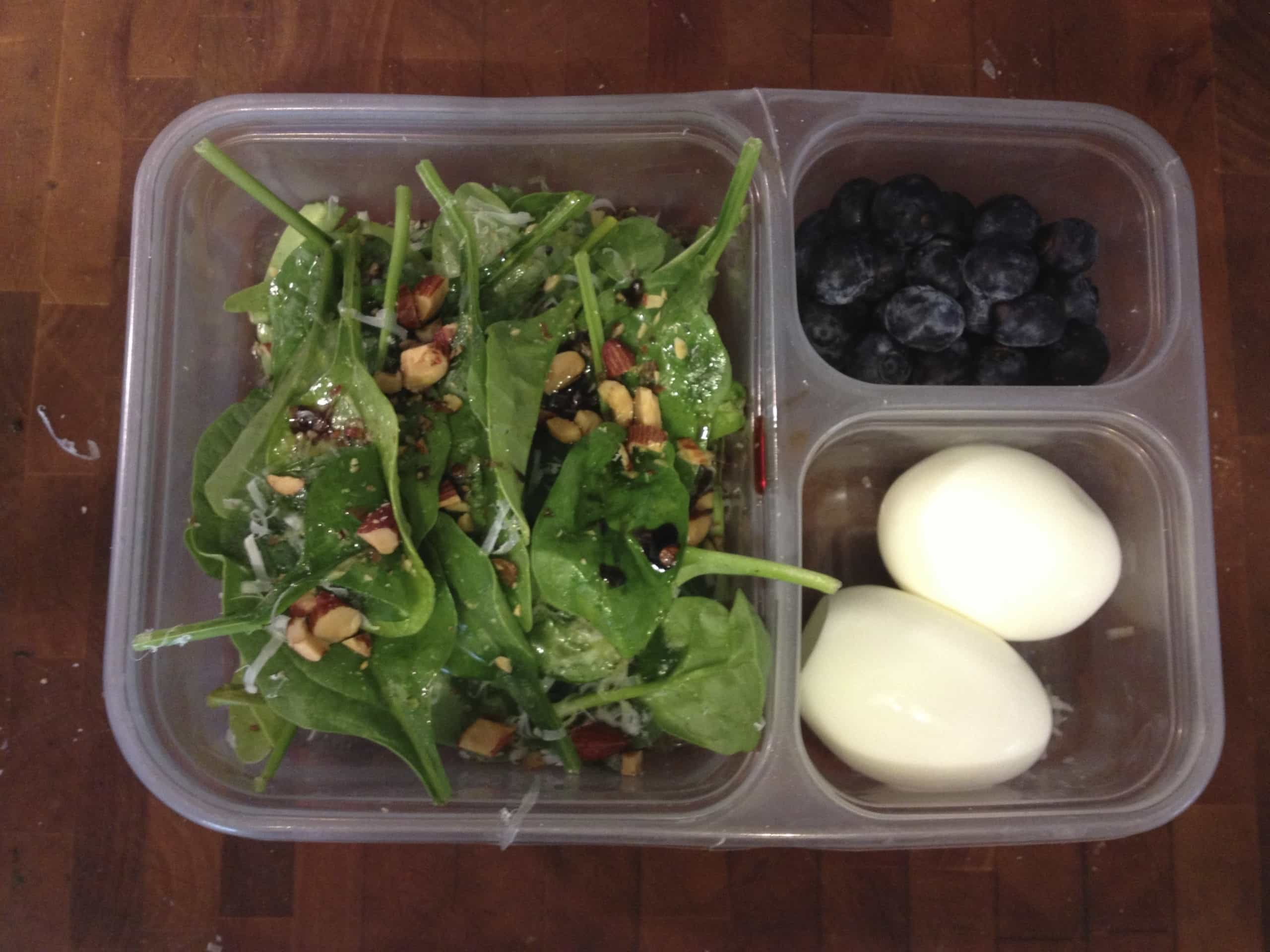 Brown bag lunch of salad, eggs, and blueberries