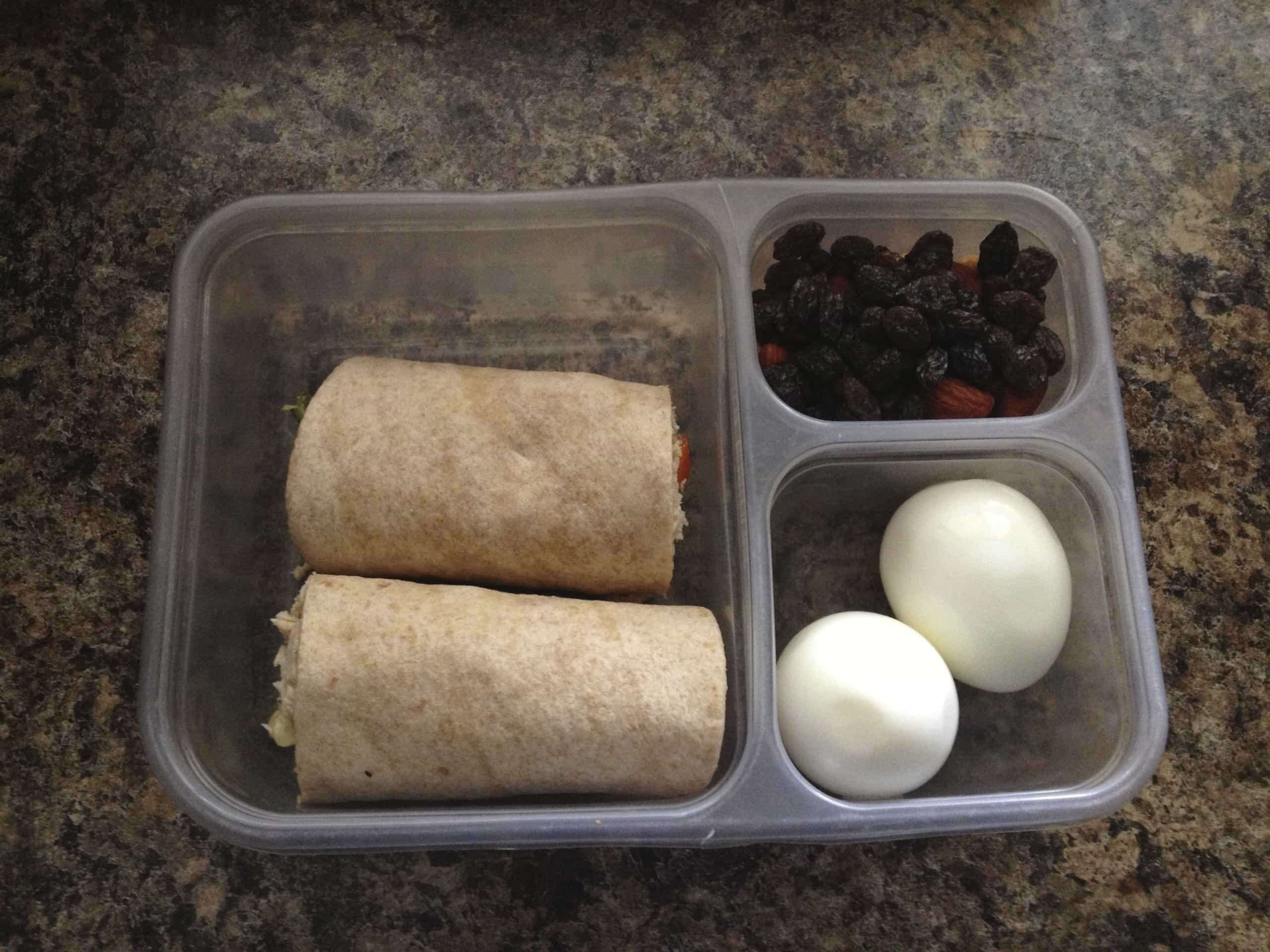 Brown bag lunch of wraps, dried fruit, and hard boiled eggs.