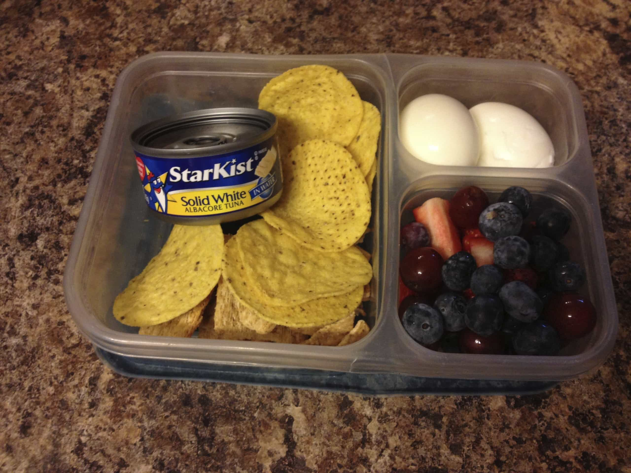 Packed lunch of tuna, fruit, and hard boiled eggs.