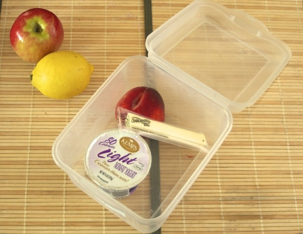 yogurt and string cheese in a storage container