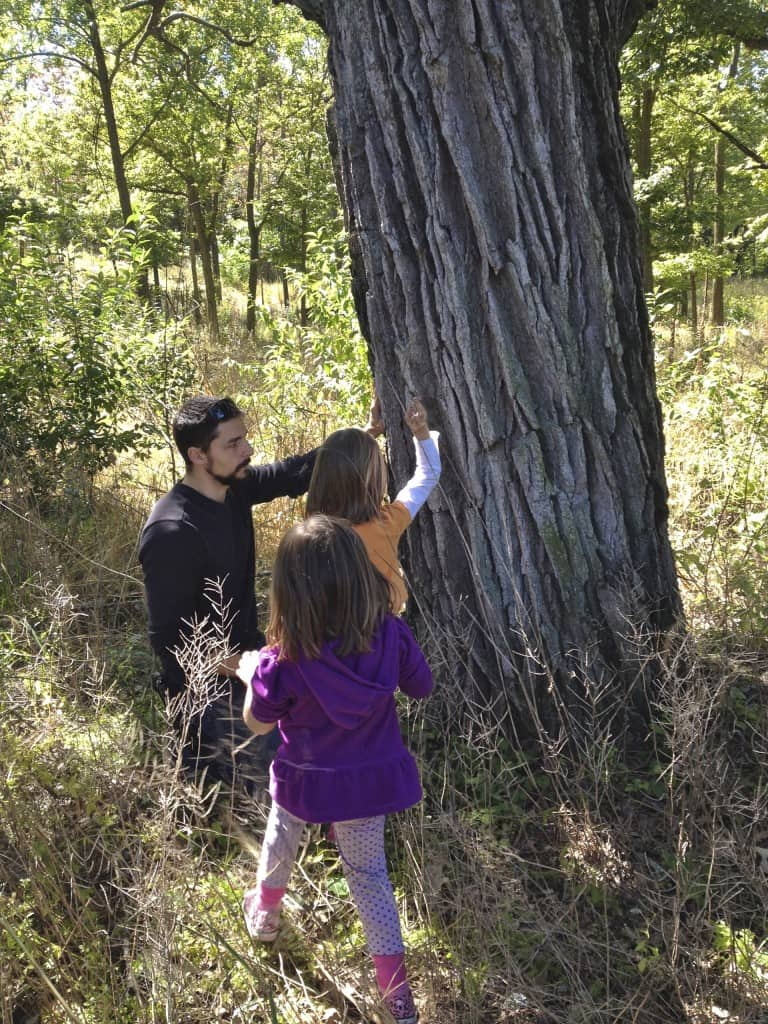 2 girls and their dad examining the bark of a tree.
