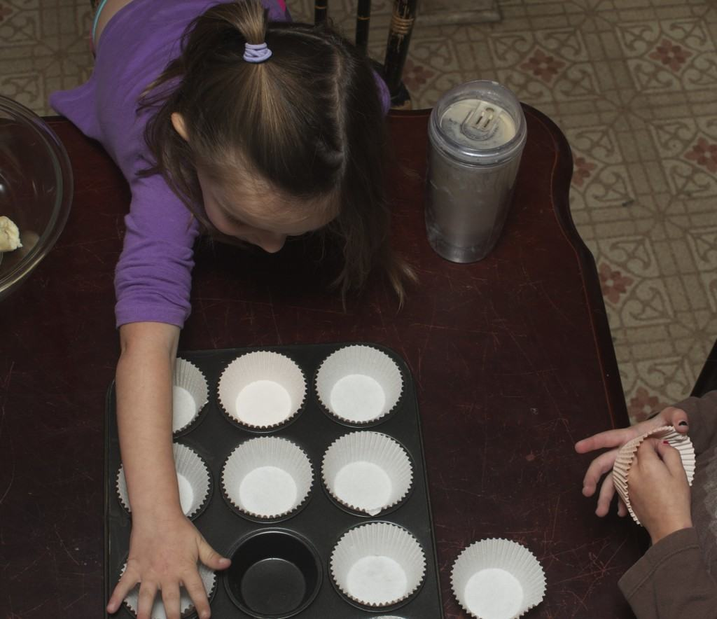 kids helping line a muffin tin