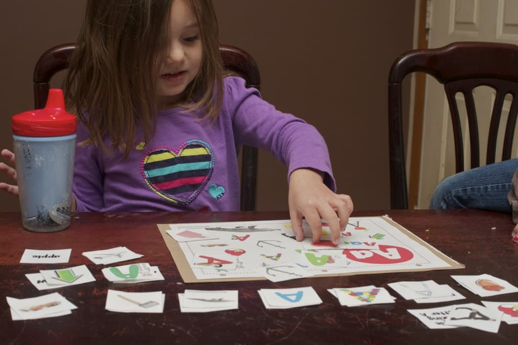 Preschooler matching up words that start with the letter A.