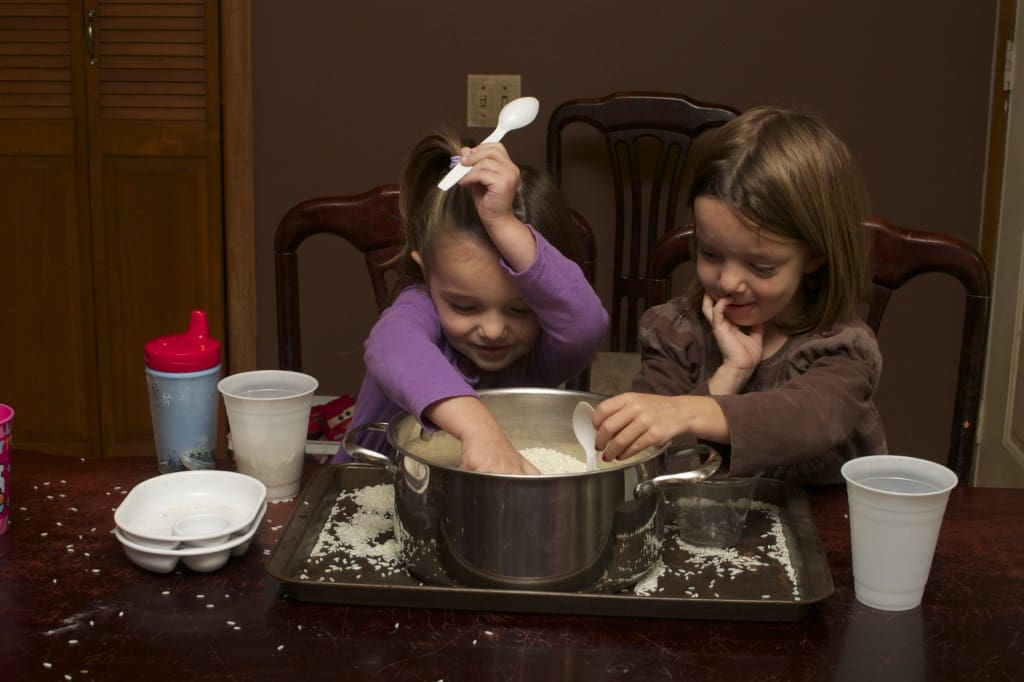 Sisters and sensory play with rice.