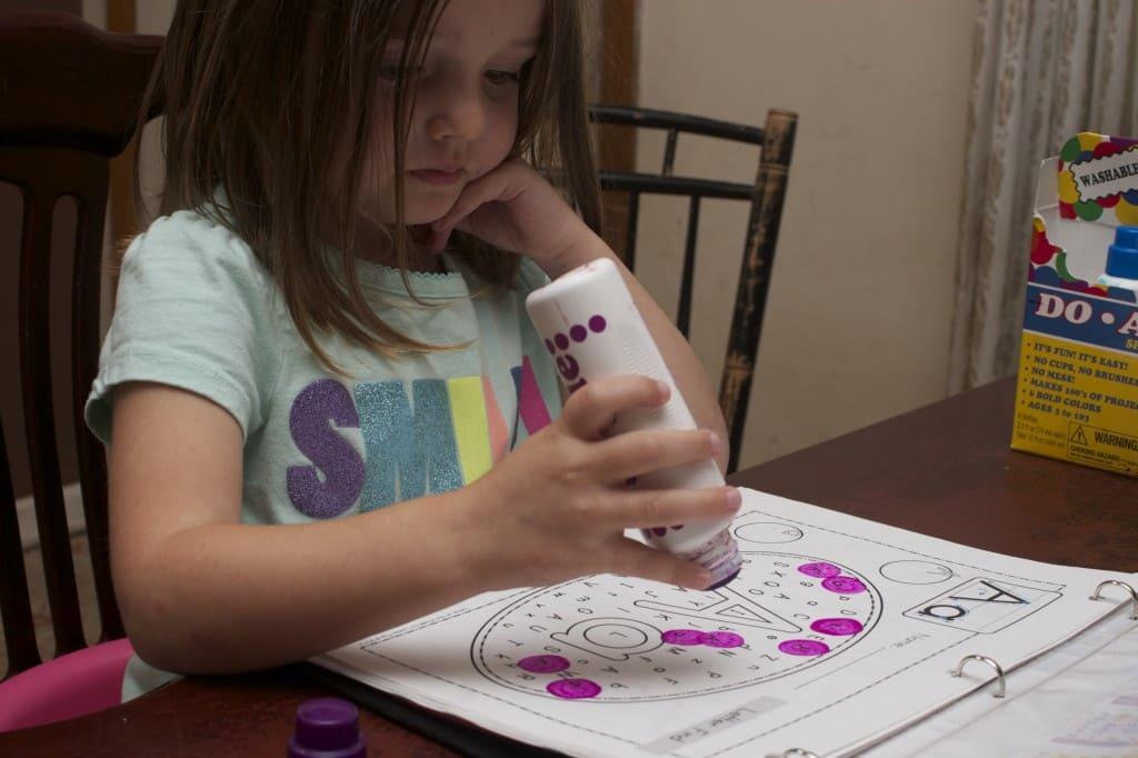 Little girl using do-a-dot markers