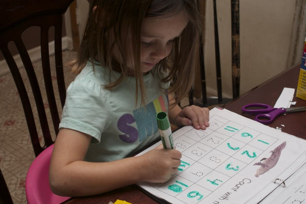 Little girl tracing numbers.