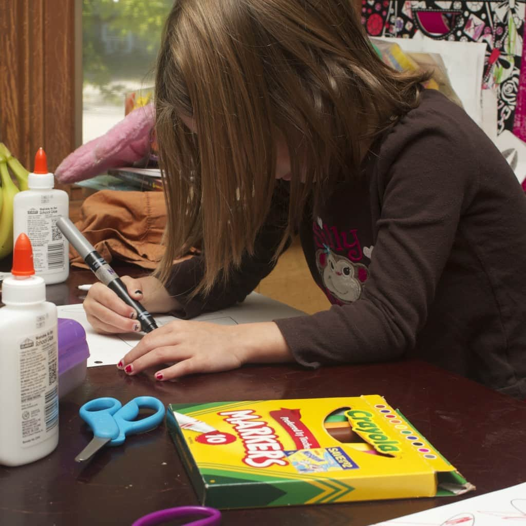 Young girl coloring with gray marker.