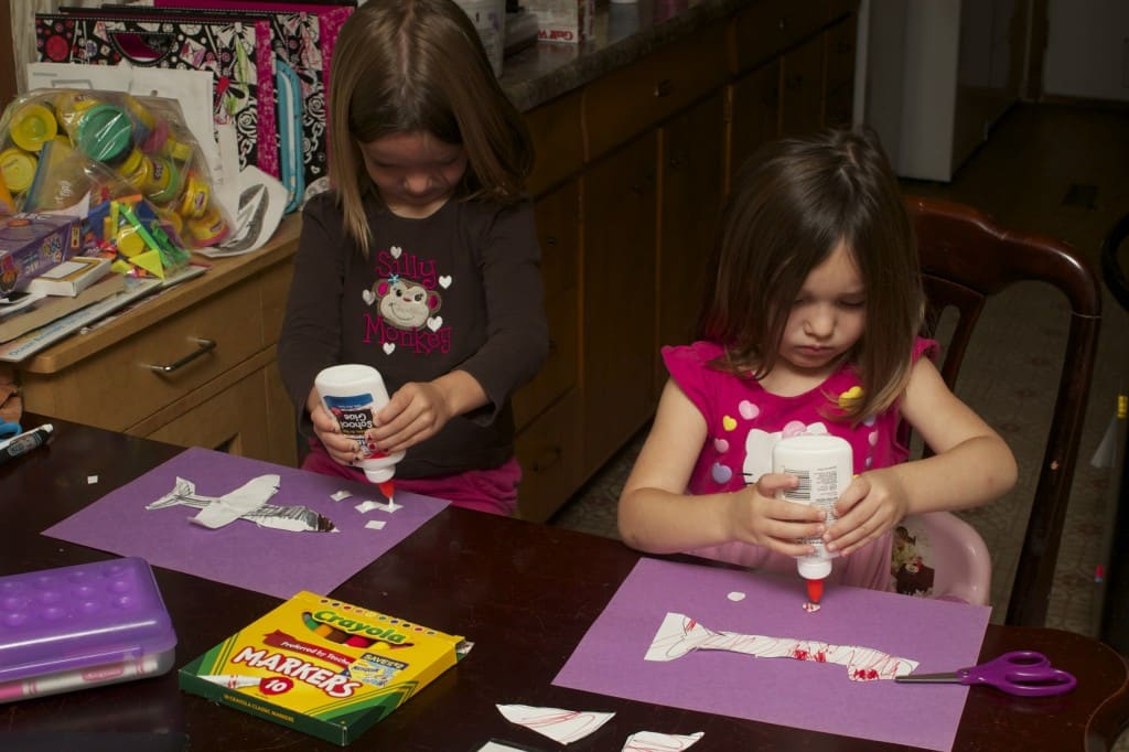 sisters crafting paper airplanes.