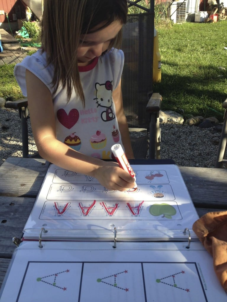 Preschooler tracing letters outside on a nice day.