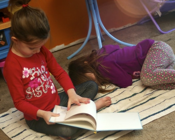 Big sister reading to her little sister