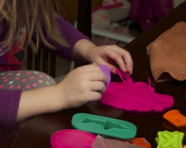 close-up of child playing with play doh