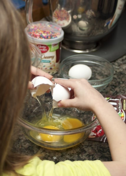 6 year old girl cracking eggs for baking.