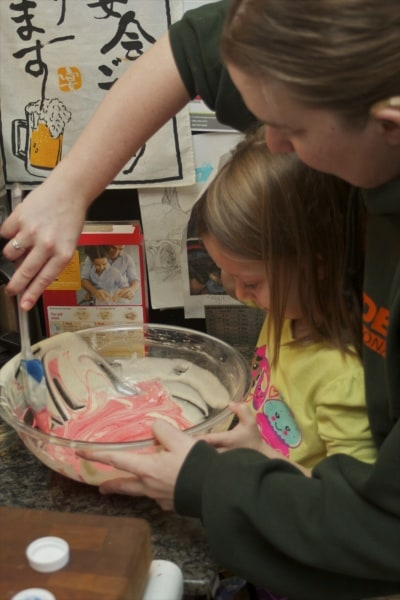 Mother and daughter mixing up a cake.