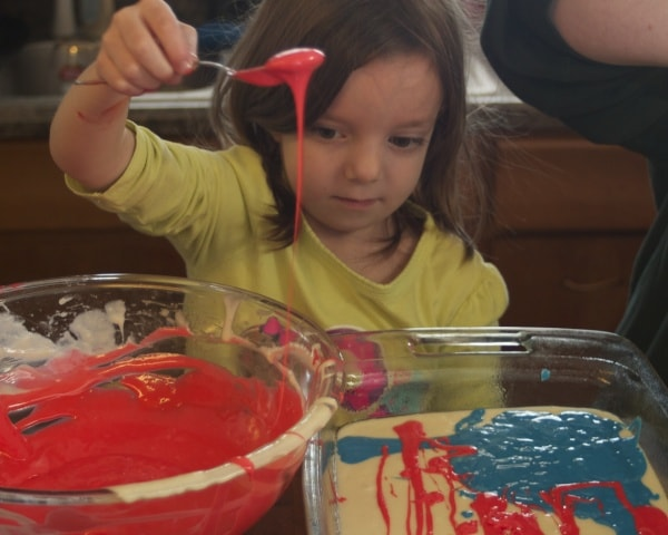 Little girl adding batter to the cake pan.