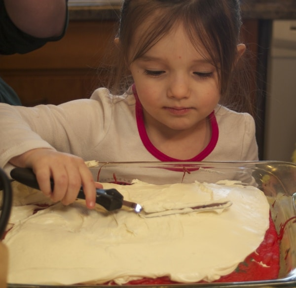 4 year old girl frosting a cake.