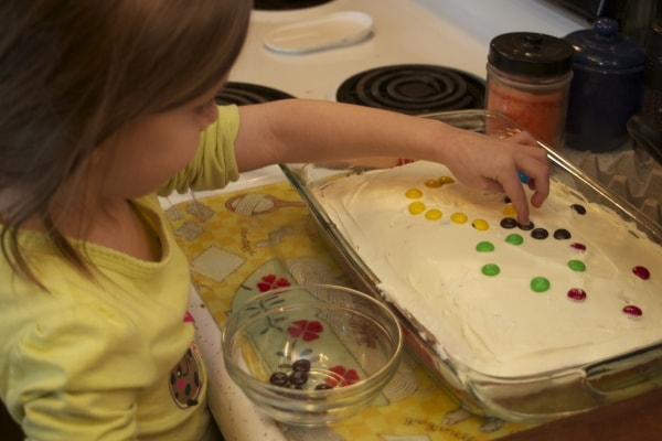 Little girl decorating a cake with M&Ms.