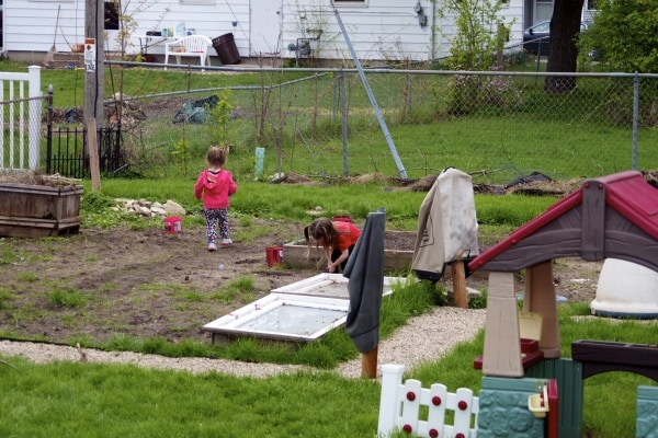 Young sisters play digging in the family garden.