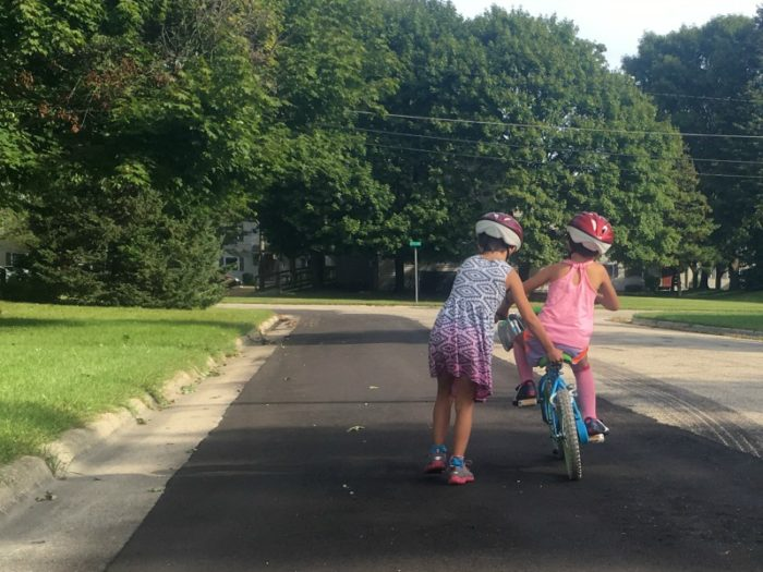 older sister helping sibling ride her bike