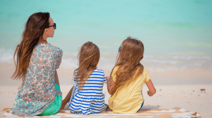 Mom and 2 daughters sitting at the beach
