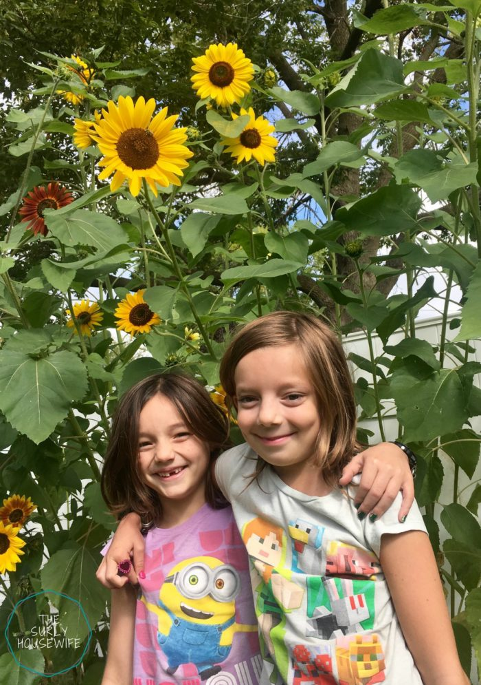 Sisters in front of sunflowers in their backyard
