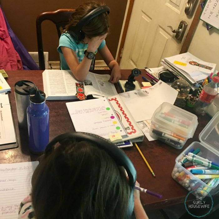 Homeschoolers doing school work at the kitchen table.