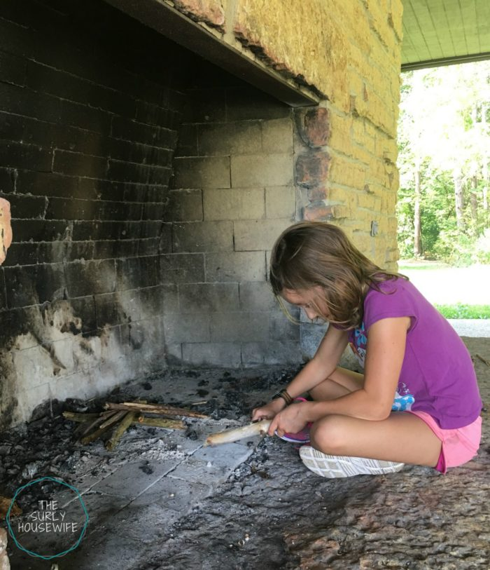 Young girl lighting a fire.