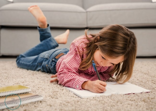 Little girl laying on floor doing her homeschool schoolwork.