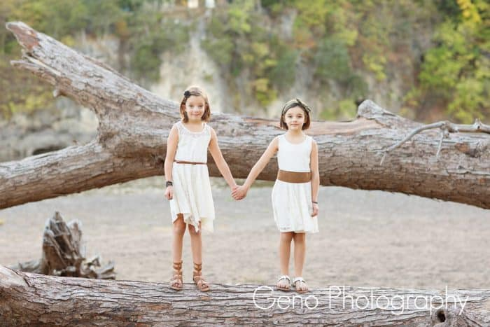 Little girls holding hands on a beached log.