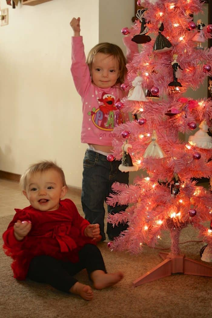 2 young sisters around a pink Christmas tree