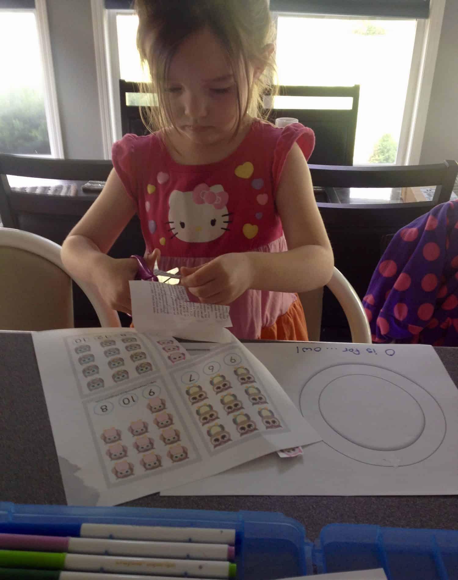 Preschooler gluing paper owls onto a big letter O