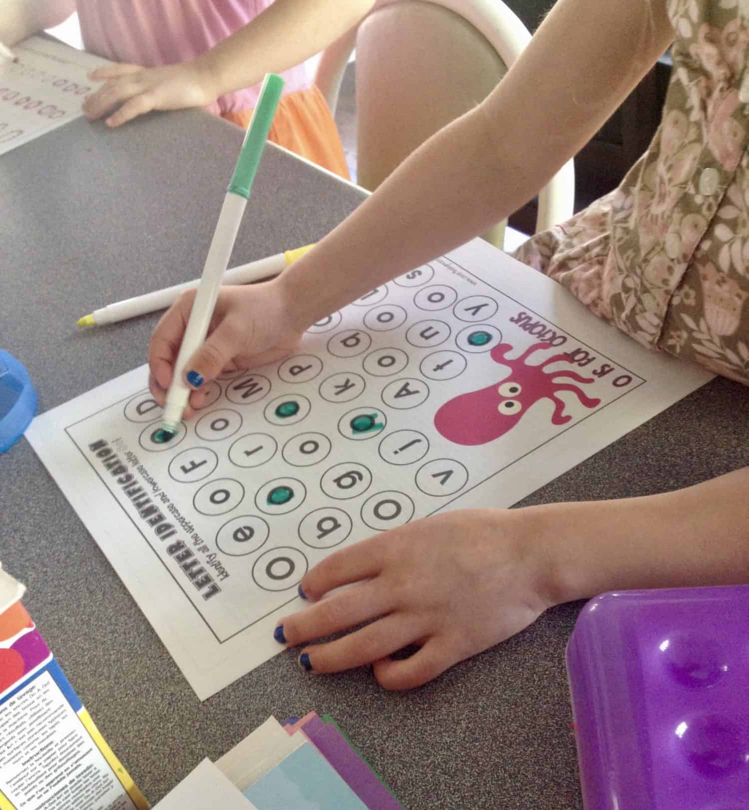 preschooler identifying the letter o on a worksheet.