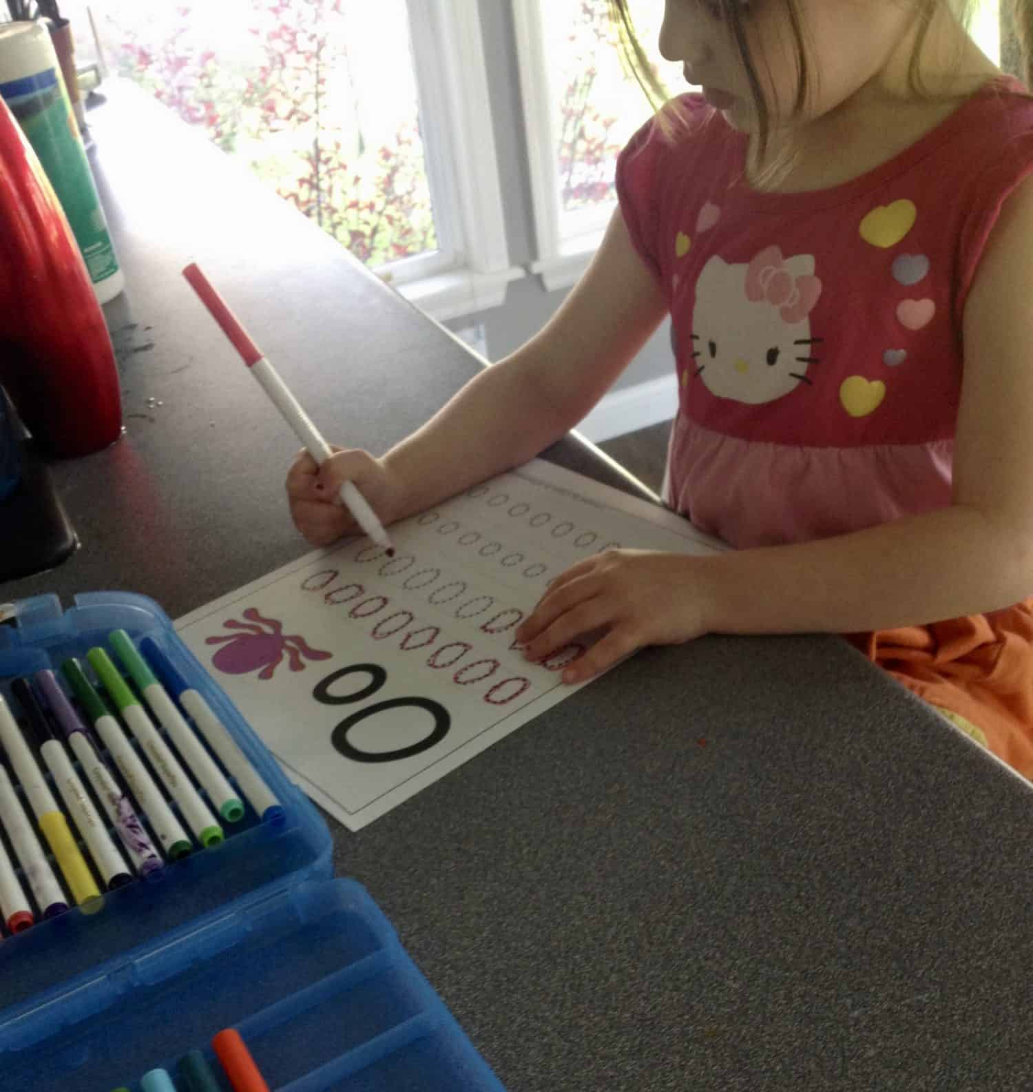 Preschooler tracing the letter o on a worksheet