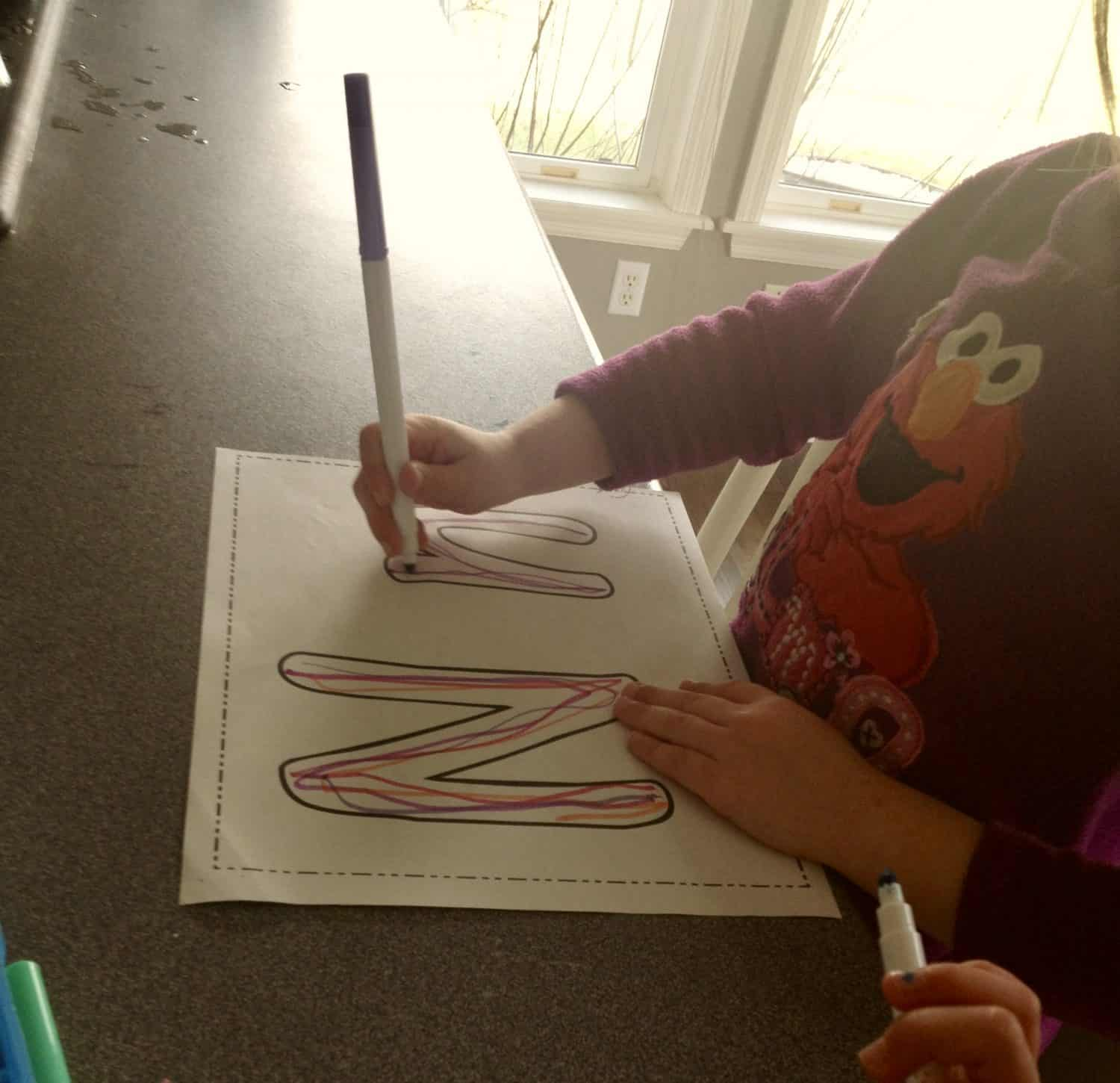 preschool girl working on writing the letter N