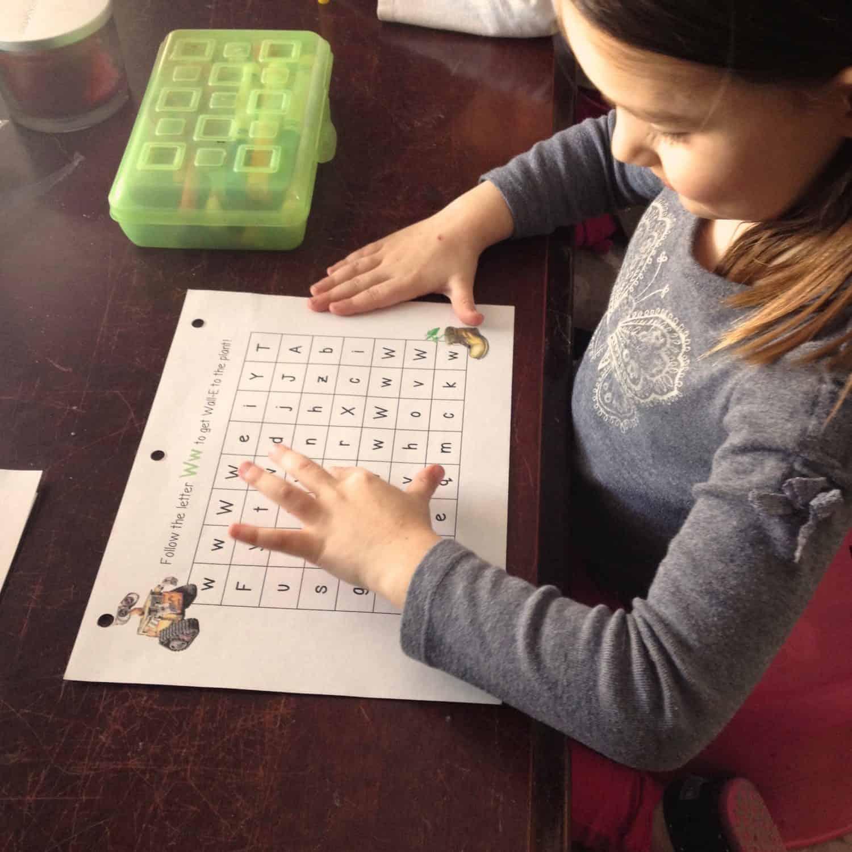 Little girl working on an alphabet maze
