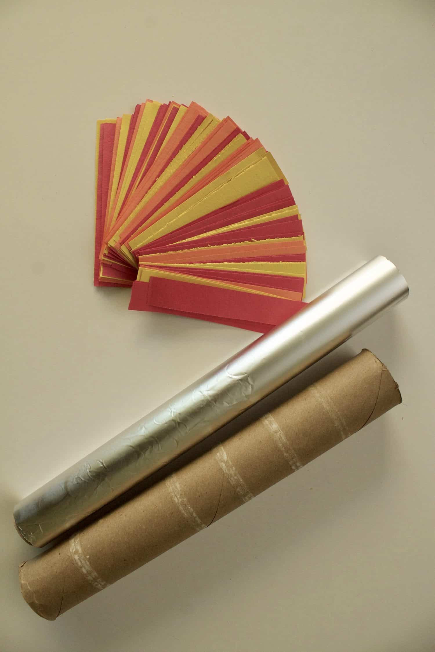 a stack of small strips of yellow, red, and orange construction paper, a roll of aluminum foil, and a cardboard tube