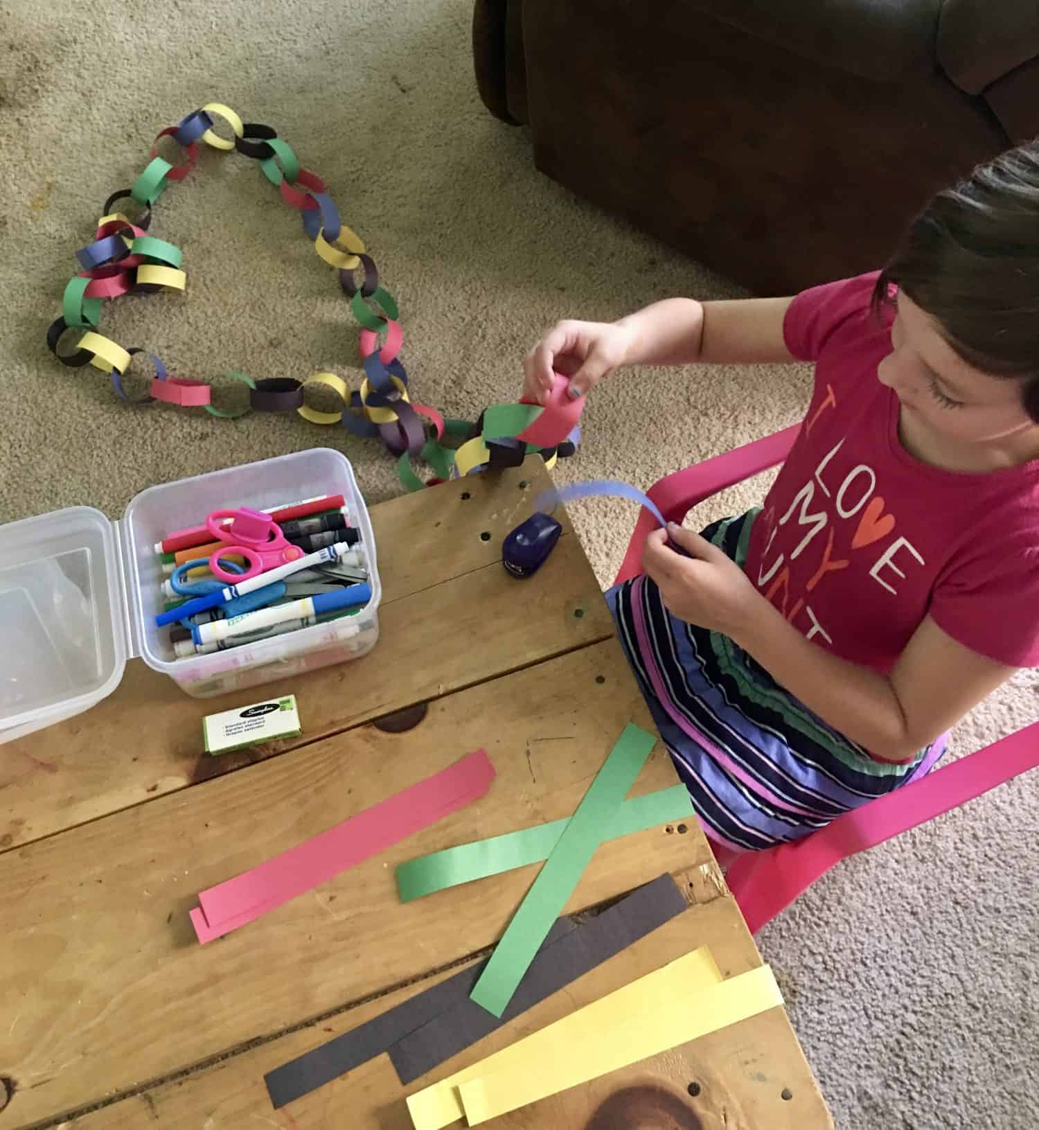 girl putting together a paper chain in the color of the Olympic rings