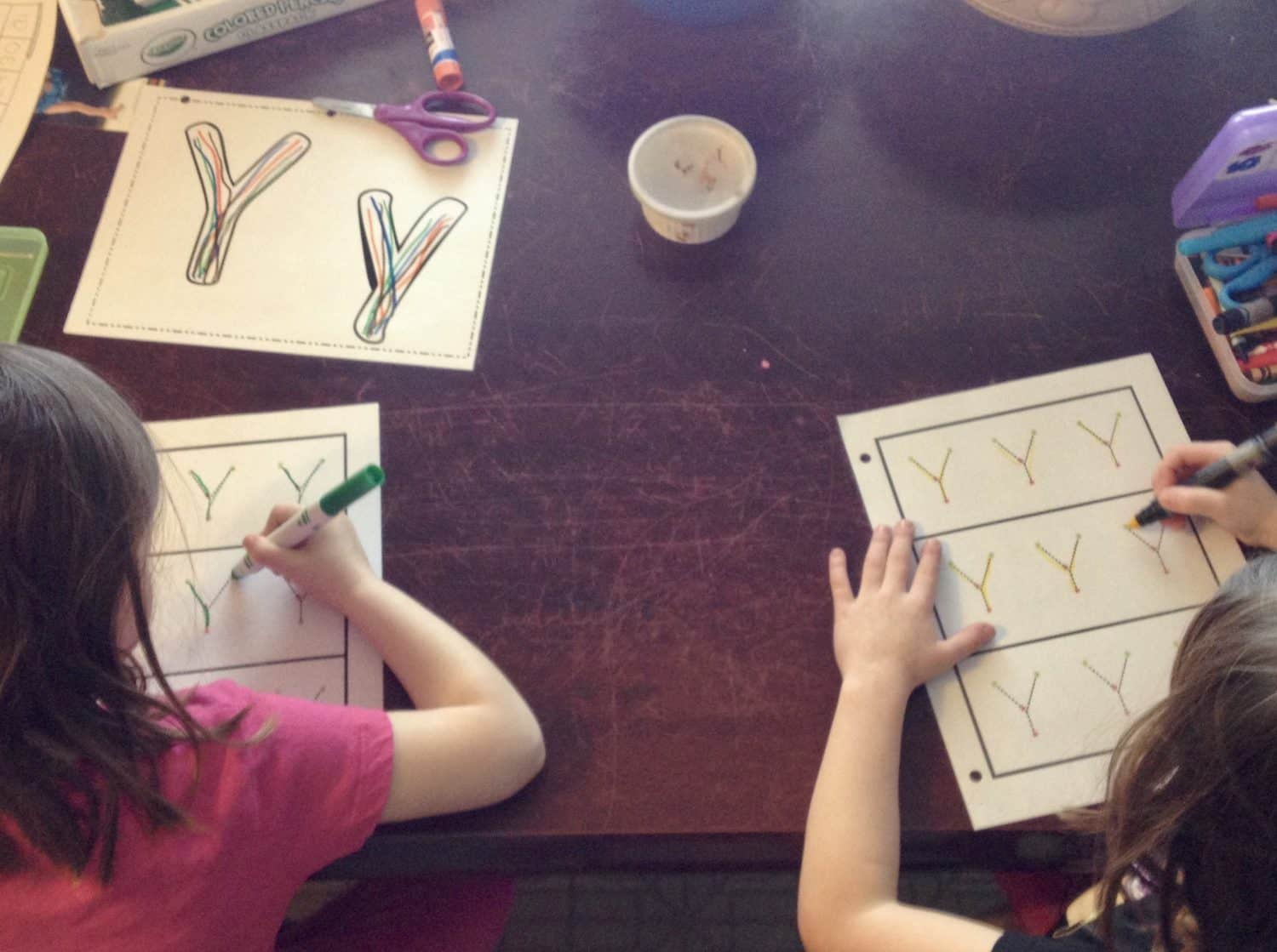 Homeschooled children working on writing the letter Y