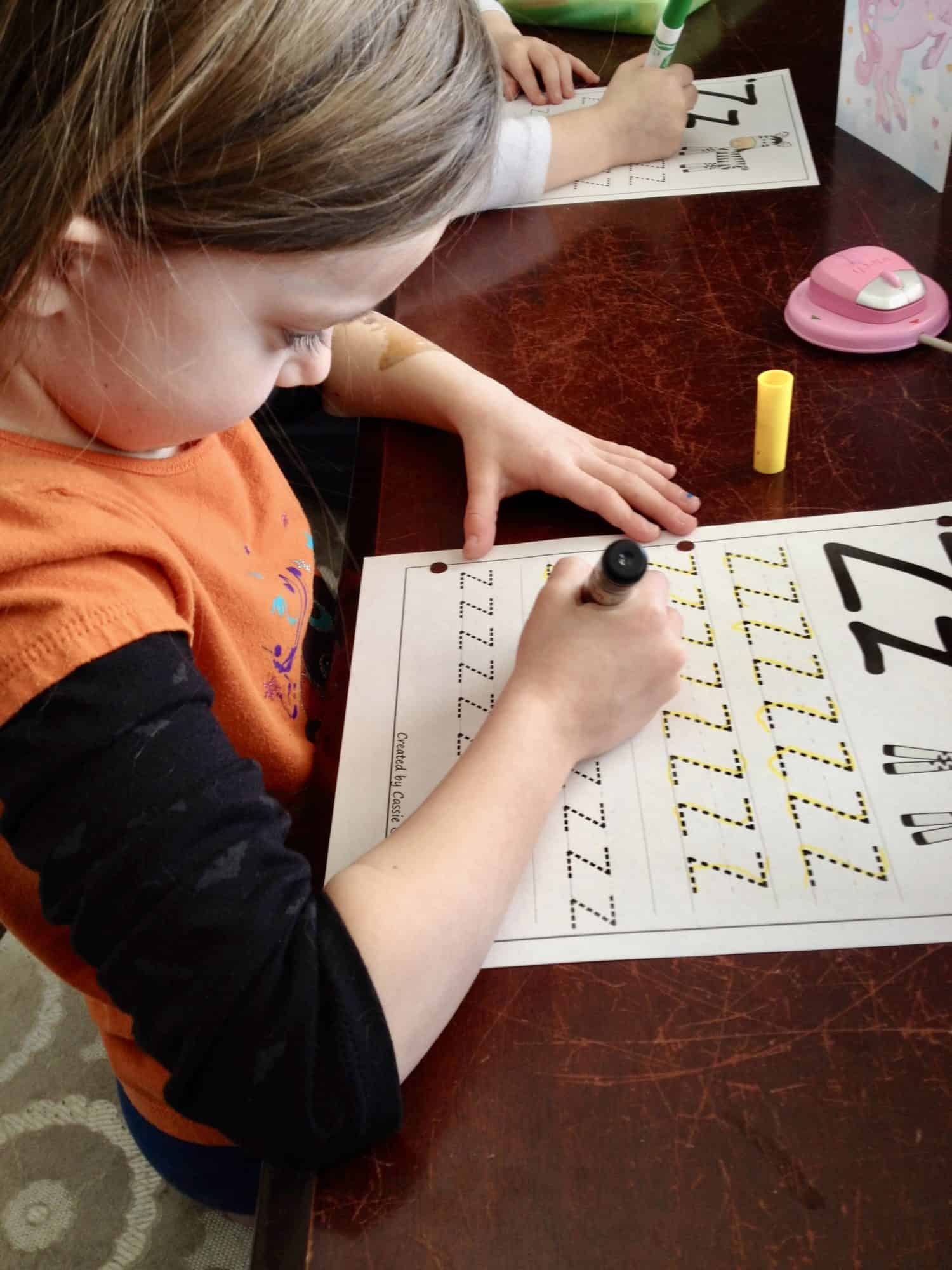 Preschool-aged girls working on tracing the letter z.