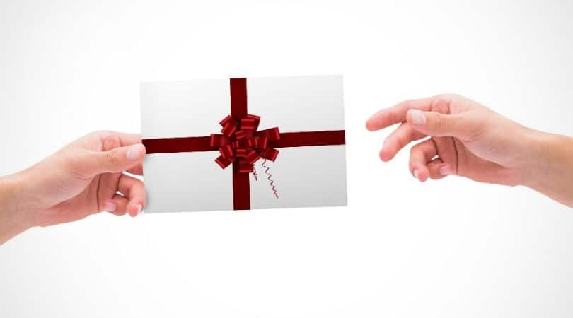composite image of hands exchanging a gift envelope