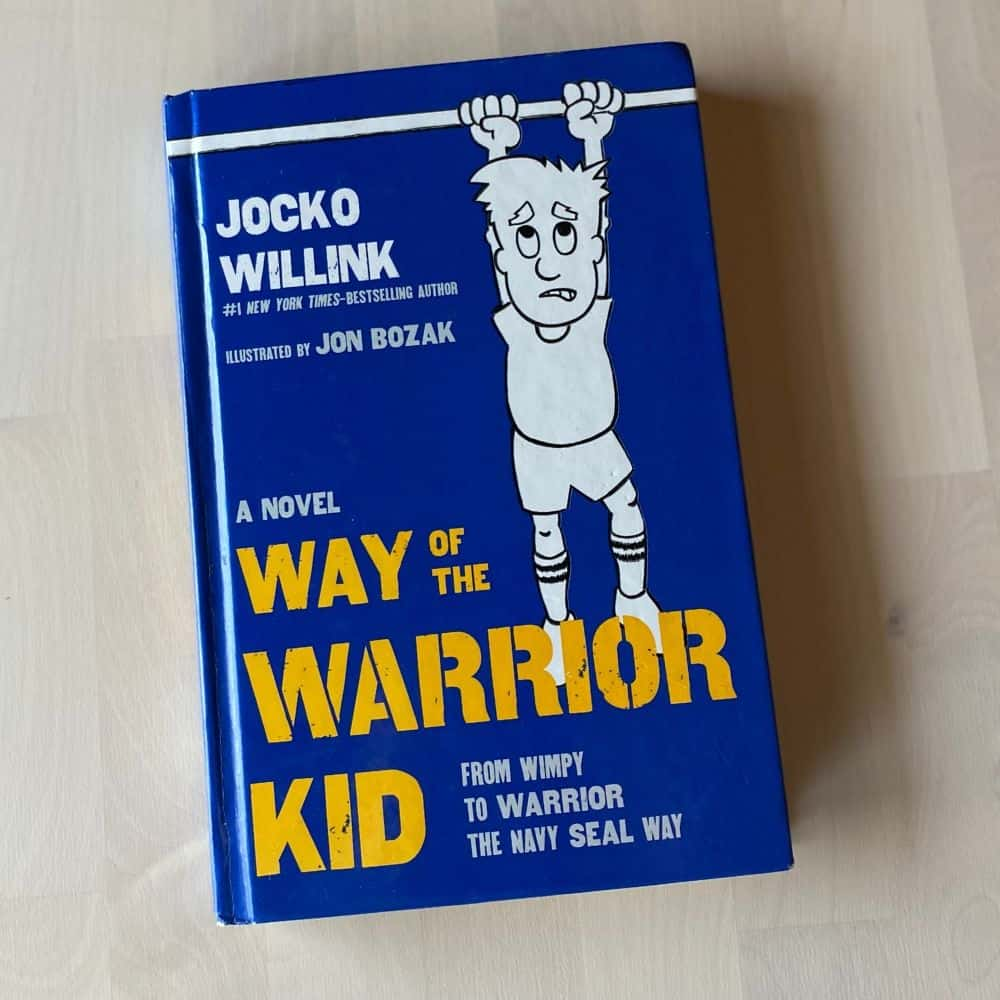 the book Way of the Warrior Kid by Jocko Willink on a wood table. Title image for blog post: My #1 Book Recommendation