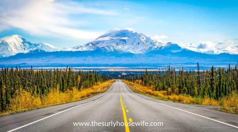 Alaska road with mountain and blue sky. Title image for blog post, 20 children's books about Alaksa