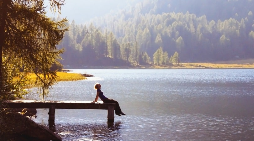 Woman relaxing on a small wooden pier at the lake.